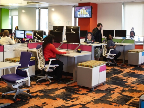 Office employees work while using Flo monitor supports at their desks.