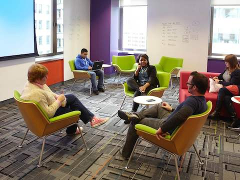 Office employees hold a discussion inside a collaborative space.