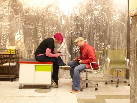 Two people converse while sitting on a Meridian cabinet and Setu chair.