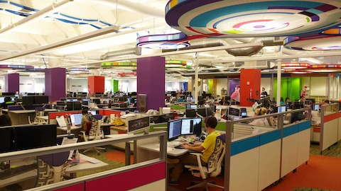 Employees go about thier work while sitting in colorful open workstations.