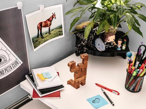 A desk space with notebooks, pens, and various personal items on the surface.