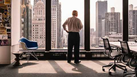 A man looks over the Chicago skyline from a high-rise office. Select to view a case study video about Slack and Company.