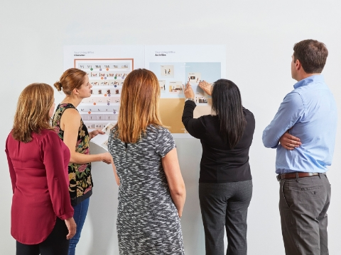 People gather to look at charts on a wall.