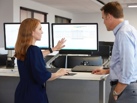 Two people talk while looking at a monitor on a standing desk.
