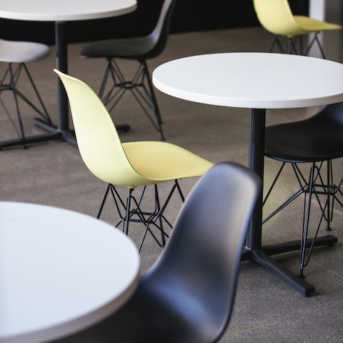 A close crop of three circular white-topped Everywhere Tables surrounded by yellow and black Eames Molded Plastic Shell Chairs.