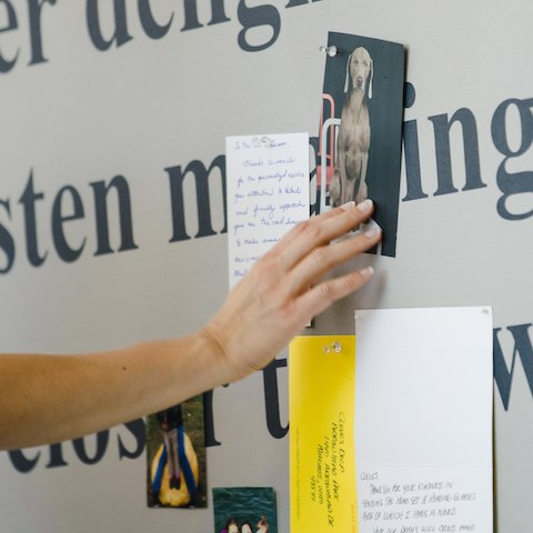 A close up of a hand tacking a photo of a dog to a board covered in a fabric with black words on it and with other notes and photos posted on it.