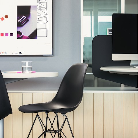 A side view of a black Eames Shell chair next to a white table with a monitor in the background.