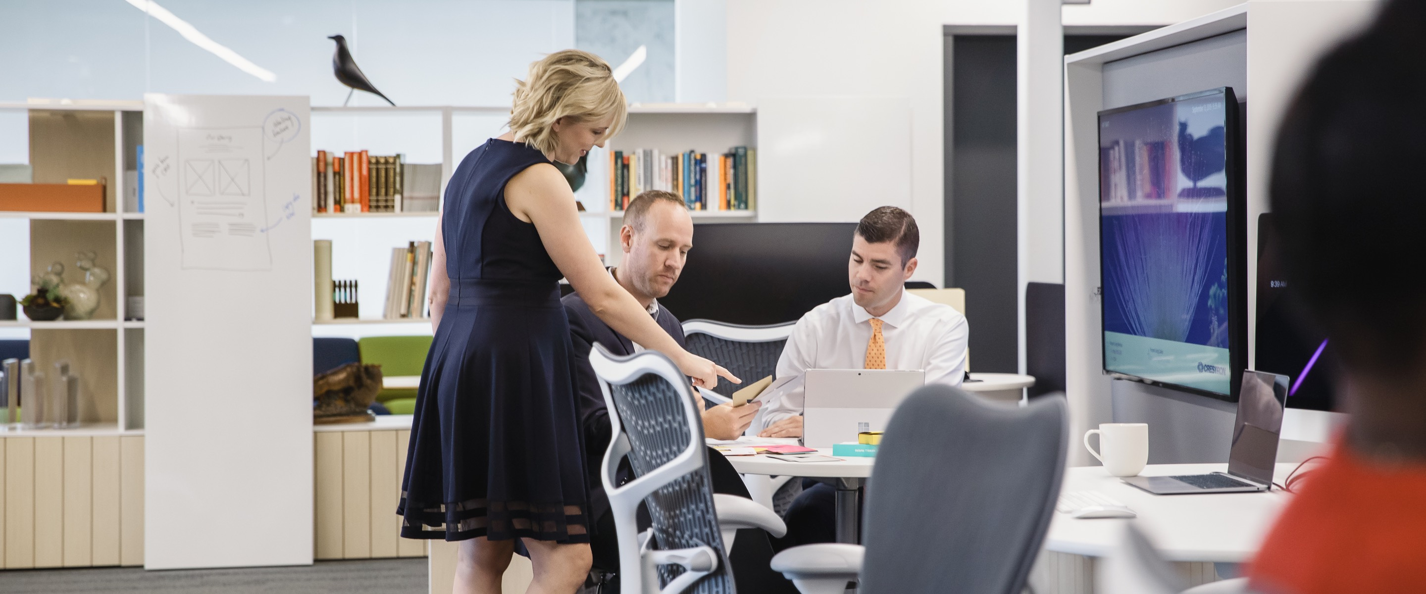Three people working together in a collaborative space with a table, gray Mirra 2 Chairs, and a monitor on the wall.