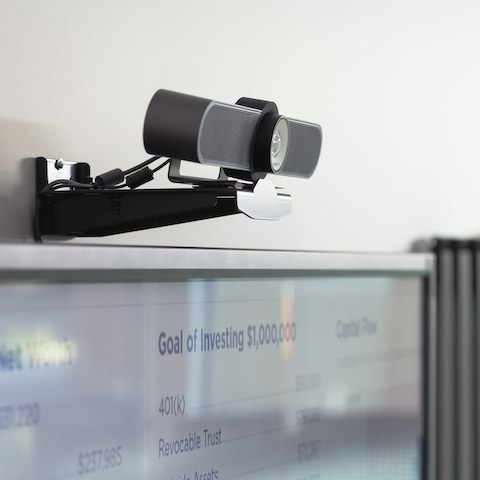 A black video camera affixed to a wall above a screen that's used for video conferencing.