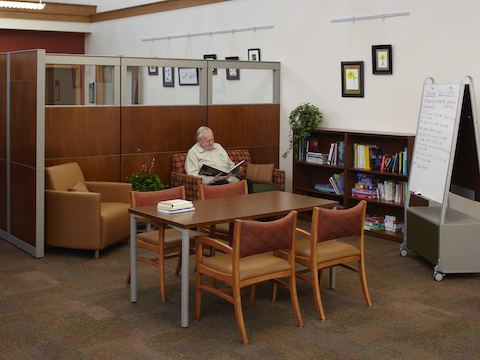 A man reads a book while seated inside of a small library area.