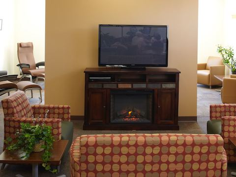 A lounge area centered around an electric fireplace and televison.