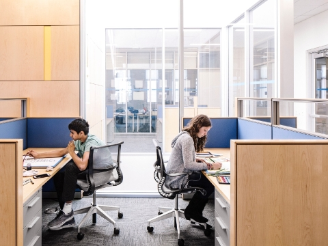 Two students study while seated at desks that offer privacy.