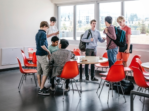 A group of students gather around a space full of tables and Eames molded chairs.