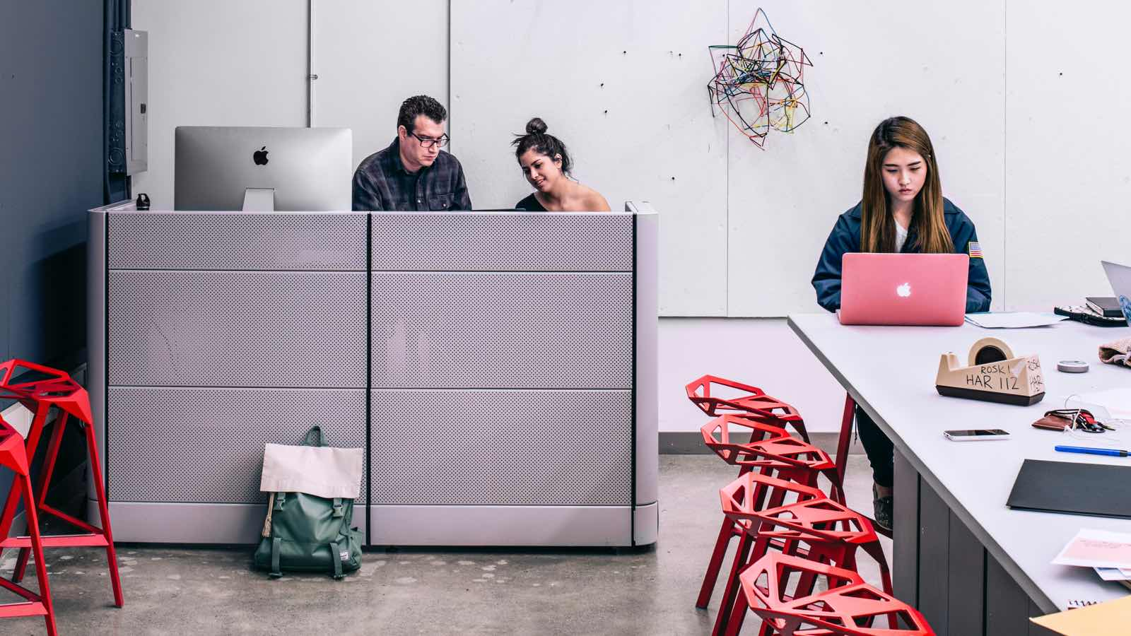 A man and woman sit behind a tall gray workstation divider with a large Apple desktop display. A female student sits nearby atop a red Magis Stool_One at a tall desk with a laptop and various office supplies.