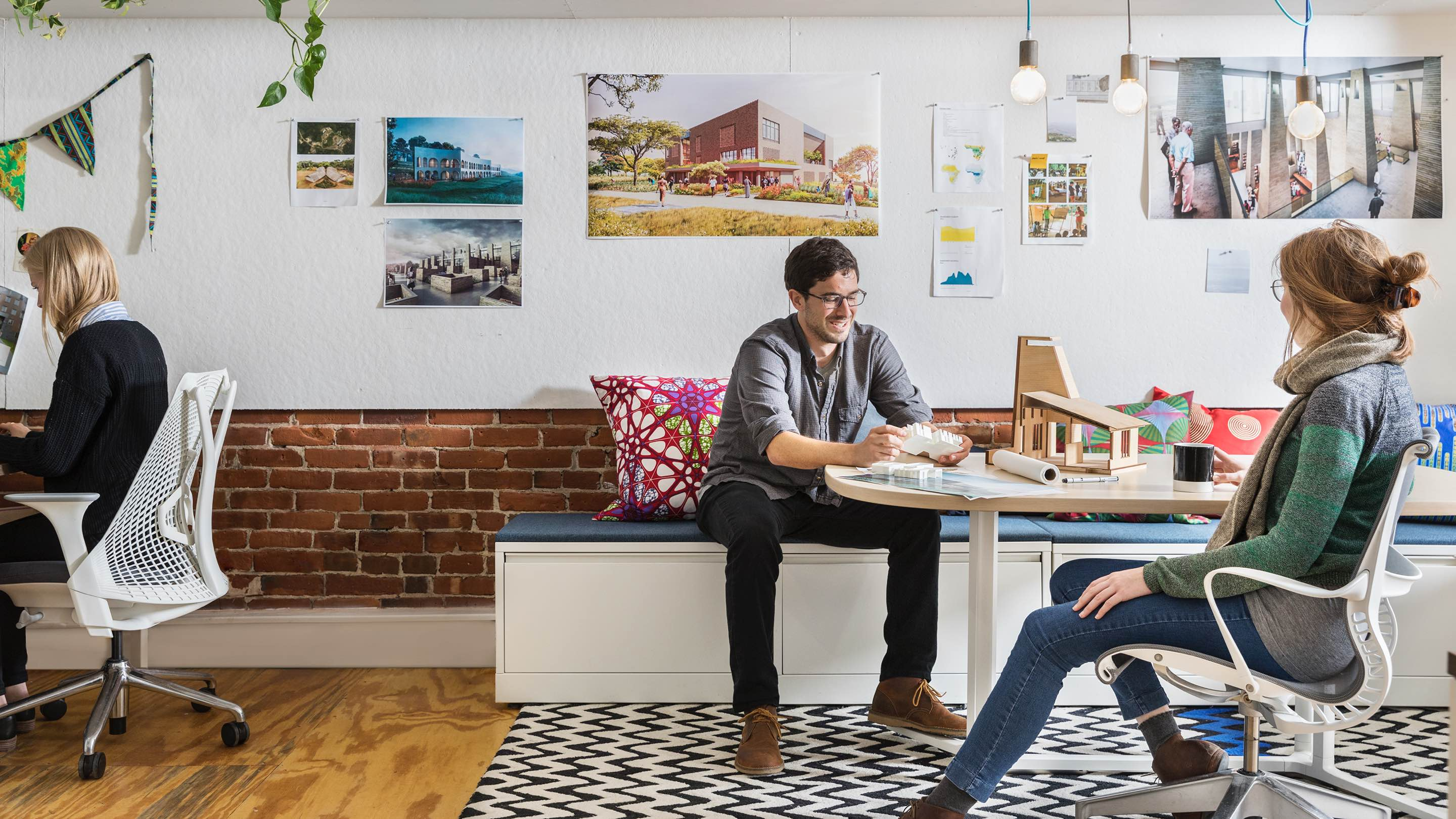 Young co-workers collaborate in an open space featuring a table, Setu office chair, and cushion-top files used as bench seating.
