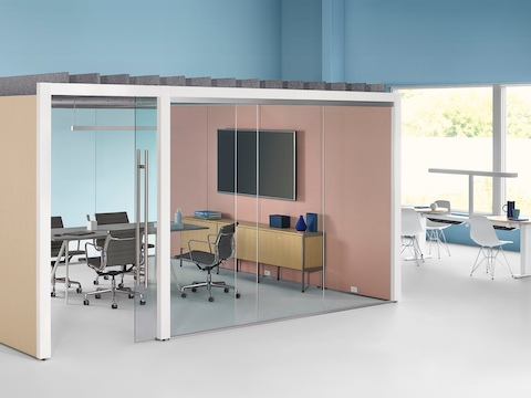 An enclosed Overlay meeting room with two glass walls and two laminate walls with a conference table and four chairs inside.