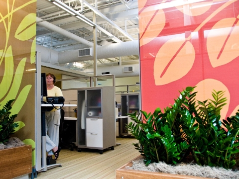 A call center employee opts to work at a standing desk rather than sitting.