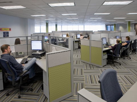 Office employees work while seated in cubicles with extended walls for increased privacy.