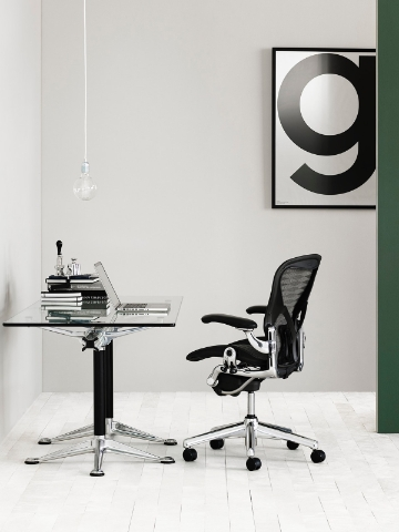An Aeron chair sits behind a glass top desk with a minimalist set up.