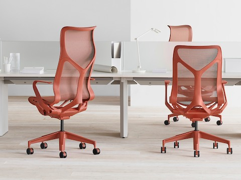 Cosm chairs in red around a workstation.