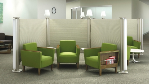 Green chairs sit within a divided waiting area inside a waiting room.