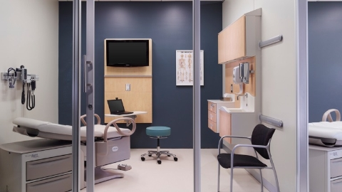 An exam room with an exam table, blue stool, black Aside Chair, and Compass System wall-hung storage.