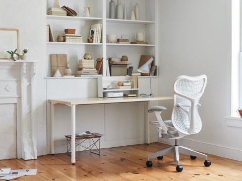 An all-white office with a white Mirra 2 Chair, white desk, Eames LTR table and bookshelves full of books and office accessories.