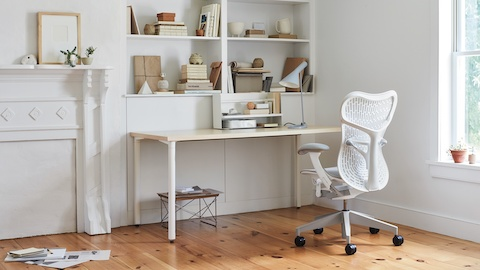 An all-white office with a white Aeron Chair, white desk, Eames LTR table and bookshelves full of books and office accessories.