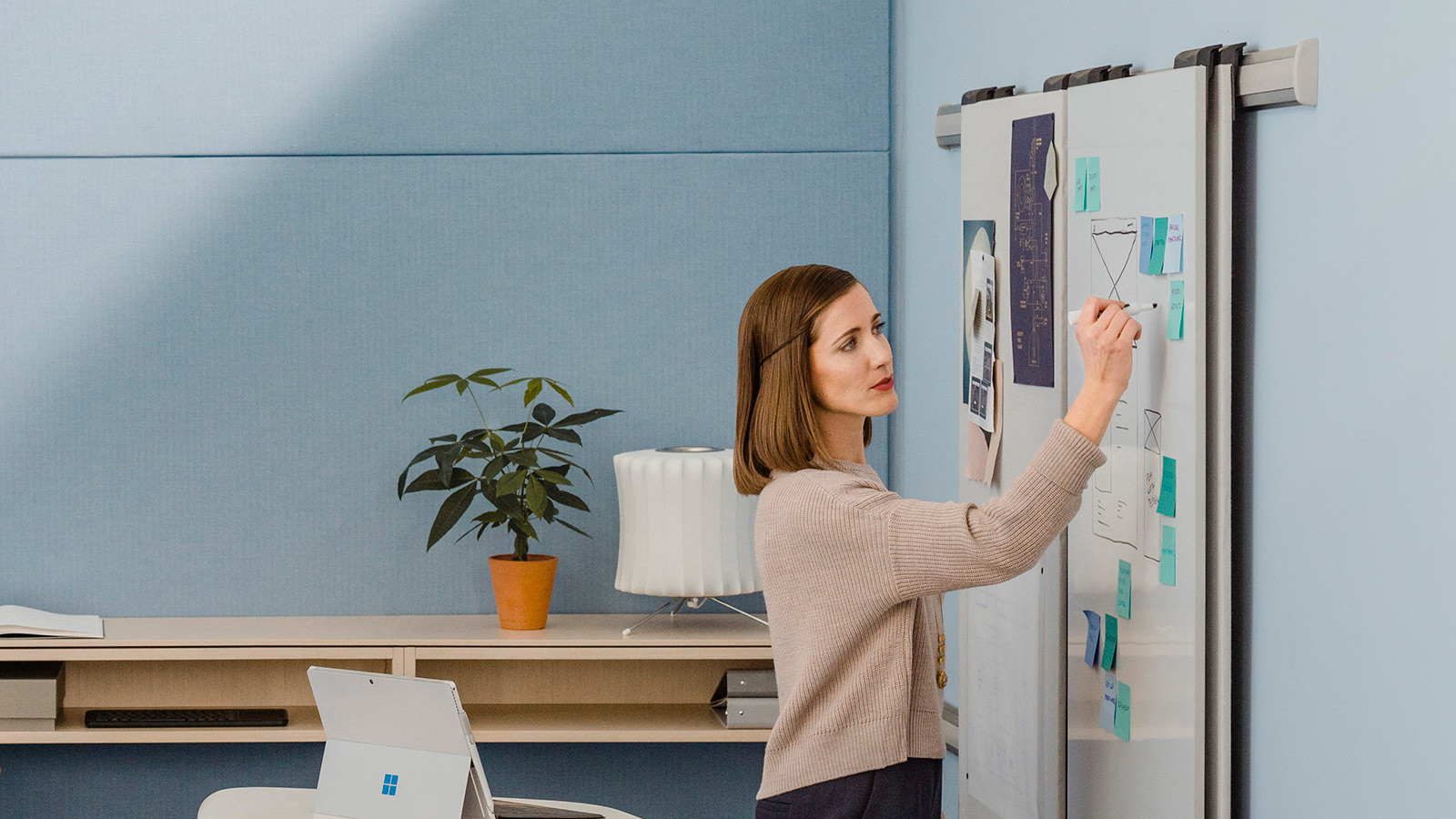 Woman in a small room with a smart board pinning project work on a board attached to a wall.