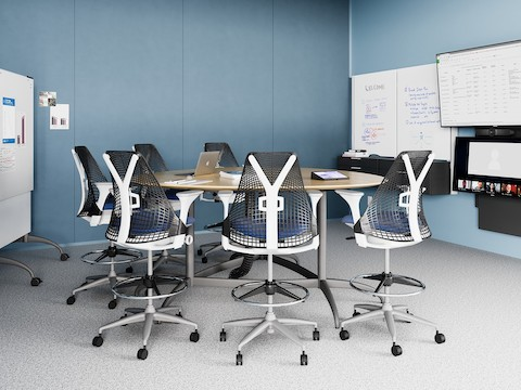 A light blue meeting space with a round table and Sayl Stools, featuring the technology from Logitech.