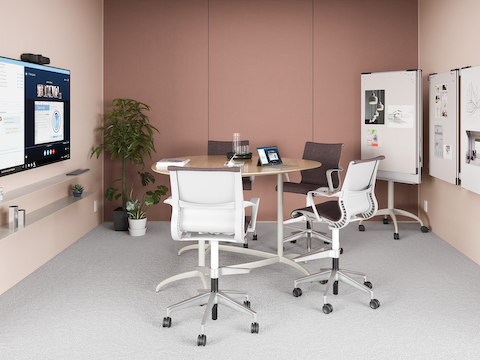 A light pink meeting space with a small table and Setu Stools, featuring the technology from Logitech.