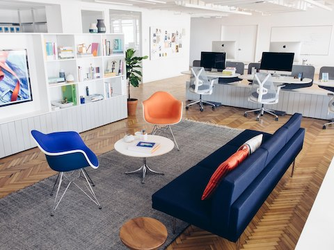 An office lounge seating area sits near several workstations in the background.