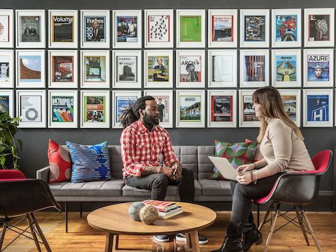 Two people talk in a lounge area with framed magazine covers and ads on the wall.