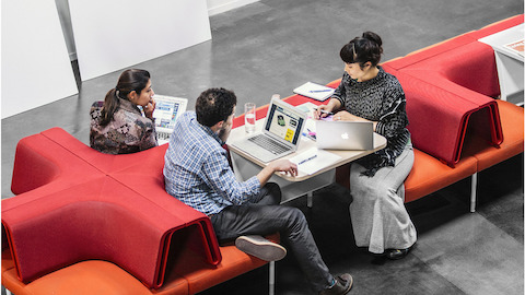 Man and two women collaborating in arrangement of red Public Office Landscape seating.