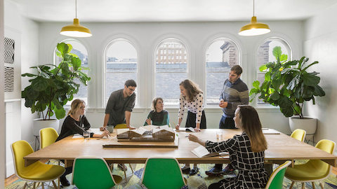 Architects at MASS Design collaborating at conference table lined with green and yellow Eames Shell Chairs.