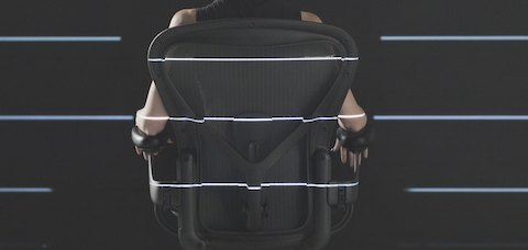 A rear view of a person sitting in an Aeron chair.