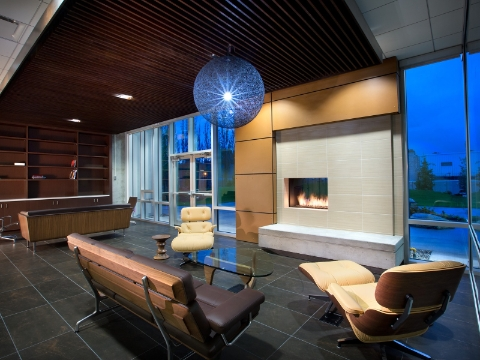 Benches and reclined seating occupy a lounge area centered around a fireplace.