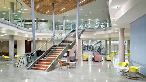 A large building lobby showcases a prominent staircase, with several lounge seating options.