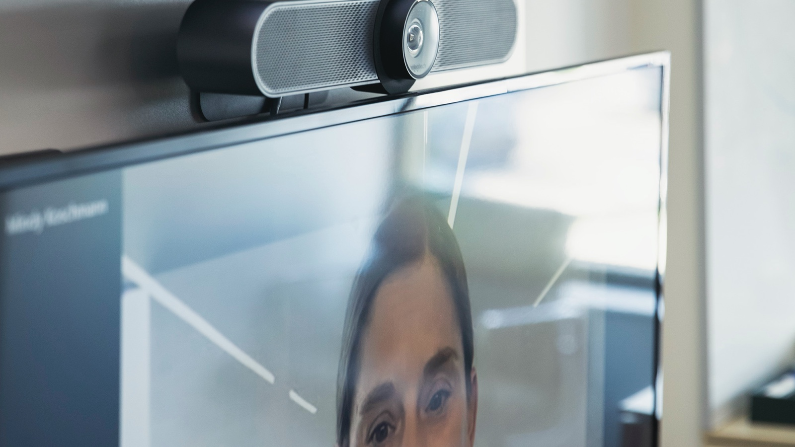 A close-up view of a display with a videoconferencing camera attached to the top.