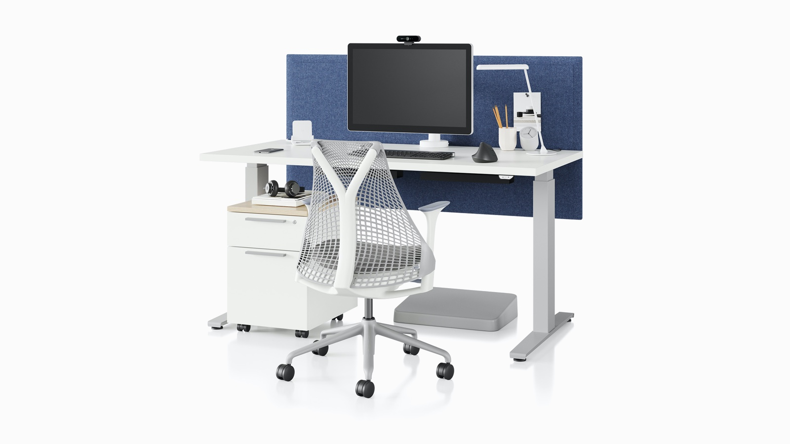 A Sayl office chair in white and a sit-to-stand desk with a blue screen.