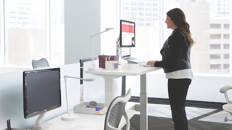 A side view of a woman standing and typing at an adjustable-height desk. Another desk with a chair and adjustable monitor is in the foreground.