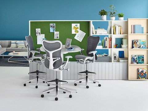 Three Mirra chairs sit at an empty table in front of shelving units.