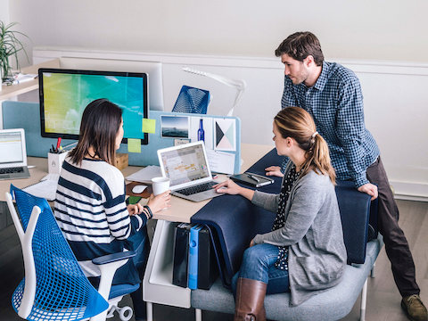 A trio of colleages gather at a desk and look at content on a laptop screen. Two sit on a Public Social Chair and one sits in a blue Sayl Chair.