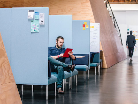 A person sits in a Public Social Chair surrounded by partitions. He's taking advantage of the privacy in the space as he catches up on emails.