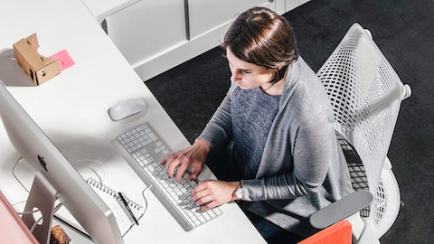 A person sits in a white Sayl Chair and types on a computer at her desk.