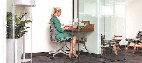 A person in green dress is sitting in a Setu Chair and typing on her laptop at a small desk in a glass-walled workspace. Spaces like this give people the opportunity to foucs on heads-down work in an open office setting.