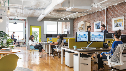 People working and collaborating at their desks in an open office setting.