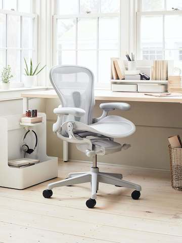 An all-white office with a mineral Aeron chair, white desk with books and papers on it, a white Ubi Mobile Bag Catch with headphones hanging, and a wire basket under the desk.
