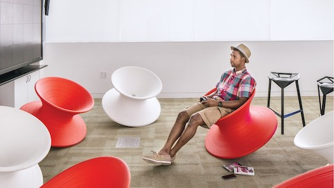 A male college student reclines in a red Magis Spun Chair surrounded by other red and white Magis Spun Chairs.