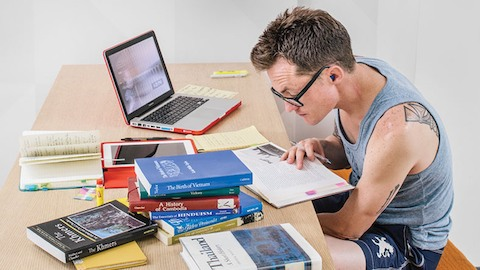 A student studies at a table piled with textbooks. Select to read a case study about California State University, Long Beach.